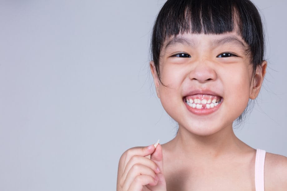 Young girl with black bangs is smiling while missing one of her front teeth.